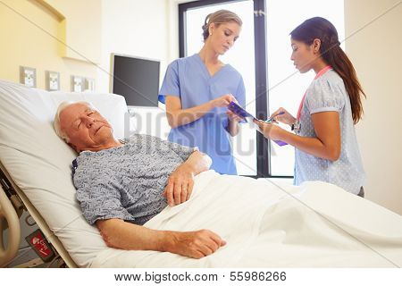 Medical Team Meeting As Senior Man Sleeps In Hospital Room