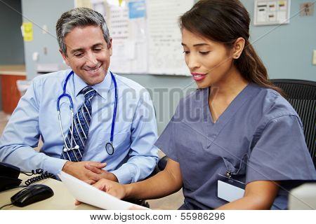 Doctor With Nurse Working At Nurses Station