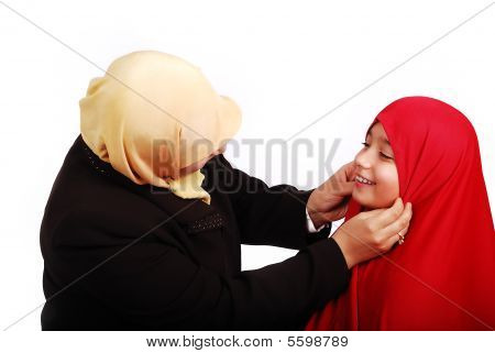 Young Muslim Female In Traditional Clothes Praying With Little Girl