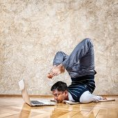 picture of locusts  - Indian businessman doing yoga and looking at laptop in the office at brown textured background - JPG