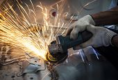 foto of hand cut  - worker hand working by industry tool cutting steel with split fire use for industrial manufacturing theme