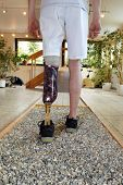 picture of amputee  - Male prosthesis wearer with lower leg amputation training to walk on loose stones in a special parcour or interior area where surfaces have been laid out to simulate realistic environmental situations - JPG
