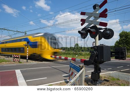 Train riding over a rail crossing in spring