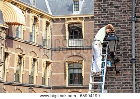 Man Correcting Lamp In Front Of Building Of Dutch Parliament - The Hague, Neherlands