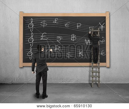 Businessman Conducting With Another Drawing Money Stave On Black Board