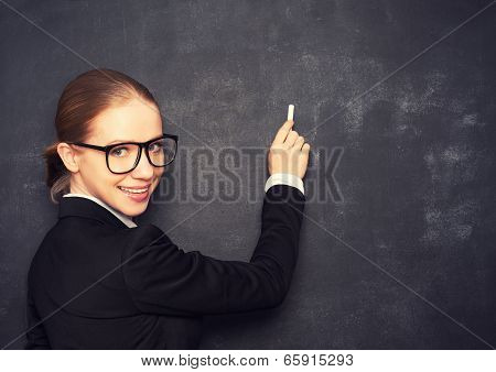 Business Woman Teacher With Glasses And A Suit With Chalk   At A School Board
