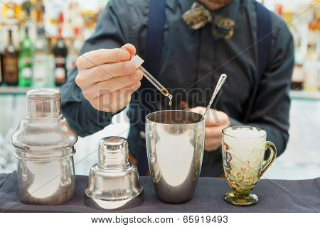 Bartender is making cocktail at bar counter, adding some bitter in the shaker