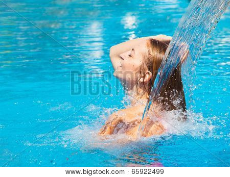 Young Woman Refresh In Pool Under The Small Waterfall