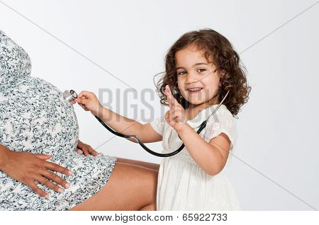 Girl Listening To Pregnant Mother's Belly