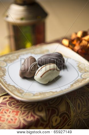 Date chocolates and a traditional lamp close up