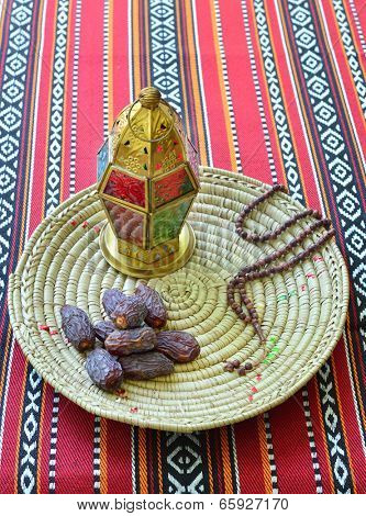 An arabic dates, lantern and prayer beads against sadu fabric background.