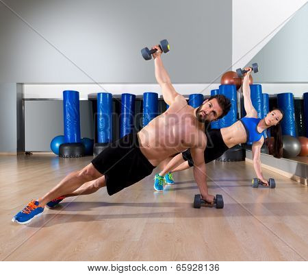 Dumbbells push-ups pushups couple at fitness gym workout