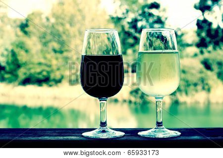 Retro Filter Style Two Glasses Of Wine, White And Red, On Wooden Rail With Country Rural Scene In Ba