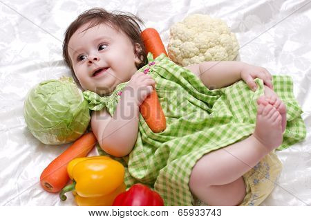 Sweet smiling little girl with green vegetables