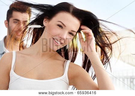 Beautiful young girl smiling at summertime, looking windswept, man behind.