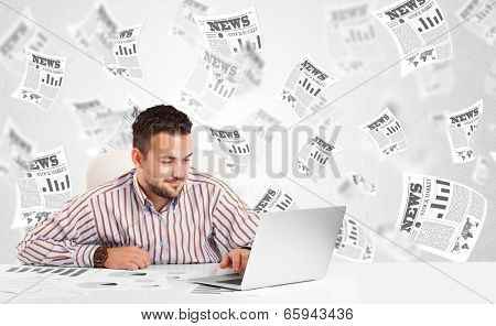 Business man at desk with stock market newspapers concept
