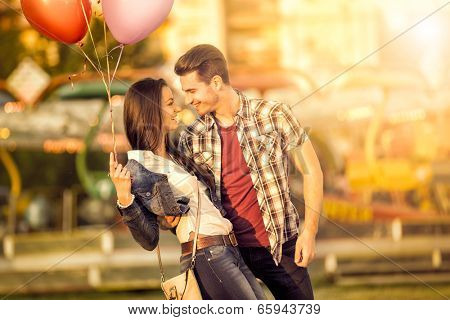 Affectionate couple having fun in amusement park laughing and looking at each other