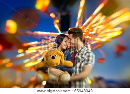 Love couple with colorful carousel in motion with sundown in background, amusement park ride - shoot with lensbaby