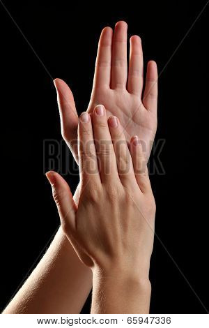 Human hands on black background
