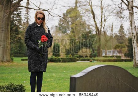 Woman Grieving At Cemetery Holding Flowers