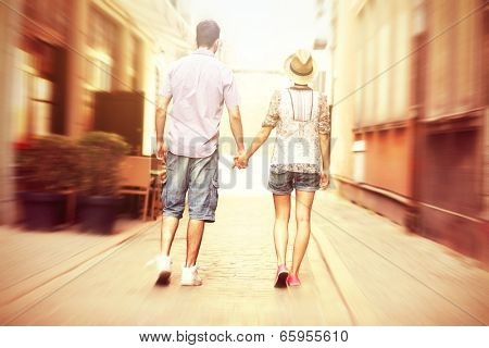 A picture of the back of a young couple strolling about the city