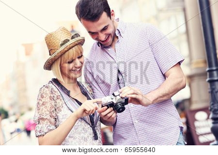 A picture of a young couple checking pictures on their camera while sightseeing Gdansk in Poland