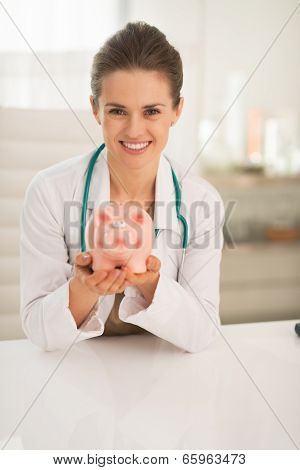 Portrait Of Happy Medical Doctor Woman Showing Piggy Bank