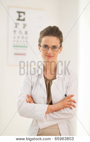 Portrait Of Ophthalmologist Doctor Woman In Front Of Snellen Chart