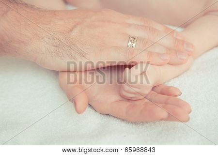 Mother And Father Hold Hand Of Baby