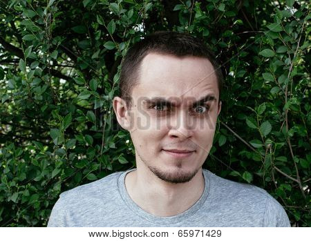 Man standing outdoors in front of green foliage raising an eyebrow in total disbelief and distrust glaring at the camera with an intense stare
