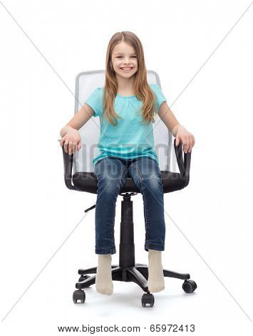 education, office and happy people concept - smiling little girl sitting in big office chair