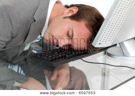Close-ep Of A Tired Businessman Sleeping On His Desk