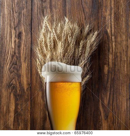 Glass of beer with wheat on wooden background