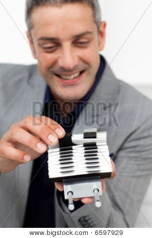 Charming Businessman Consulting A Business Card Holder
