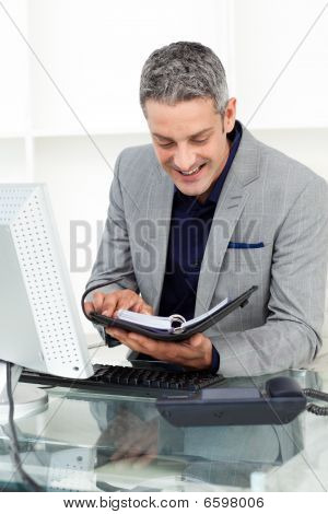 Smiling Businessman Consulting His Agenda