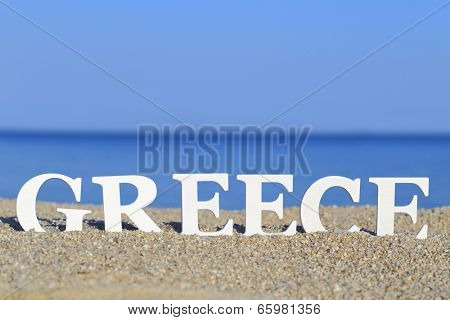 Seascape with white word Greece on the sand