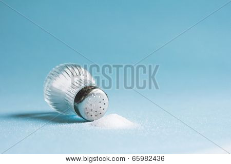 Spilled salt and saltshaker on blue background