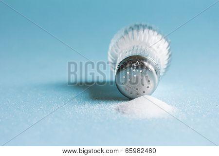 Spilled salt and saltshaker on blue background