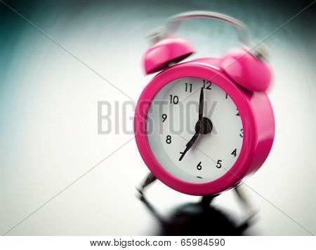 Pink Alarm Clock Ringing On Bedside Table
