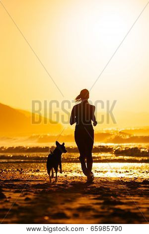 Woman And Dog Running On Beach At Sunrise