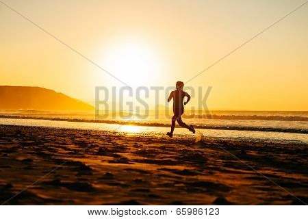 Female Athlete Running On Sunset At Beach