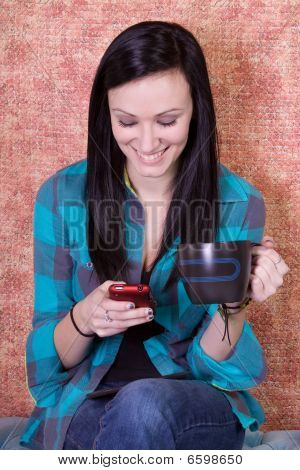 Smiling Teenager Drinking Coffee And Texting