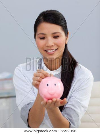 Asserive Businesswoman Saving Money In A Piggybank