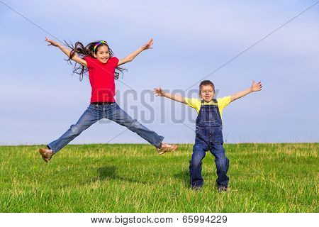 Jumping kids on green field