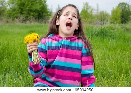 Sneezing girl on meadow with dandelions