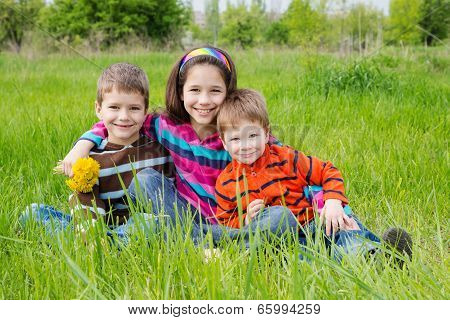 Three smiling kids on green meadow