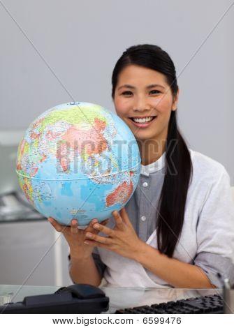 Assertive Asian Businesswoman Holding A Globe