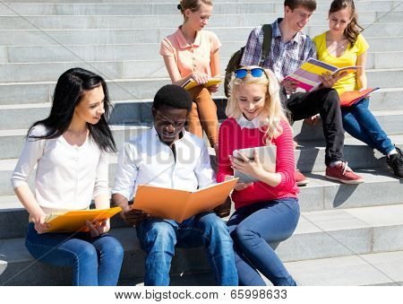 Group of university students studying reviewing homework