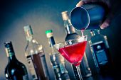 stock photo of bartender  - Barman pouring a red cocktail into a glass with ice on blue light disco atmosphere