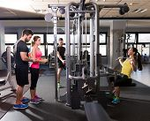 pic of gym workout  - cable pulley system gym workout fitness people with personal trainer - JPG